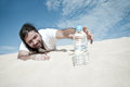 Thirsty man reaches for a bottle of water in the desert Royalty Free Stock Image