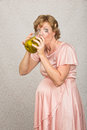 Thirsty pregnant woman ashamed drinking vinegar from pickle jar Royalty Free Stock Images