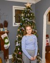 Thirteen year old girl posing in front of the Christmas tree in her home in Saint Louis, Missouri Royalty Free Stock Photo