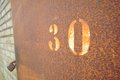 Thirty a locked rusted metal door with faded numbers stenciled Stock Photography