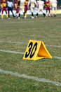 Thirty yard line of a football field with blurred players in the background Stock Images