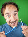 Thirty year old man with braces and a toothbrush over green background Royalty Free Stock Images