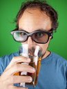 Thirty year old man with d glasses drinking and watching a movie while over green background Royalty Free Stock Photography