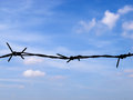 Thorn wire deterrent freedom by barricade on blue sky Stock Images