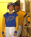 Thoroughbred jockeys alberto delgado and saul arias arcadia ca feb left wait in the paddock for their mounts for the st race at Stock Image