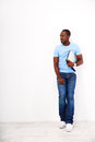 Thoughtful african man standing with laptop over white background Stock Photo