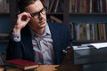 Thoughtful author young working at the typewriter and adjusting his eyeglasses while sitting at his working place with bookshelf Royalty Free Stock Photo