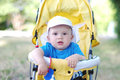 Thoughtful baby boy age of months on yellow buggy carriage Stock Photo