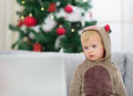Thoughtful baby in deer suit near Christmas tree Royalty Free Stock Photo