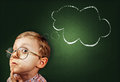 Thoughtful boy funny portait with abstract idea clouds on chalkboard Royalty Free Stock Image