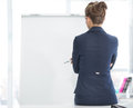 Thoughtful business woman standing near flipchart rear view Royalty Free Stock Photography