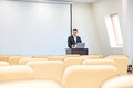Thoughtful businessman with laptop in empty conference hall writing speech on Stock Images