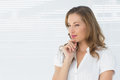 Thoughtful businesswoman looking away against blinds Royalty Free Stock Image