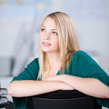 Thoughtful businesswoman looking up while sitting on chair closeup of young at office Stock Image