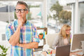 Thoughtful casual designer in front of his working colleague the office Stock Image