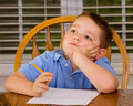 Thoughtful child doing his homework at kitchen table at home Royalty Free Stock Image