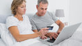 Thoughtful couple using their laptop to buy online at home in bedroom Royalty Free Stock Photography