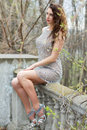 Thoughtful curly brunette in luxury grey dress sitting on handrail Stock Photos