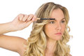 Thoughtful curly haired blonde using eyebrow brush on white background Stock Photos