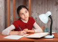 Thoughtful cute girl doing homework table Royalty Free Stock Images