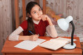Thoughtful cute girl doing homework table Stock Image