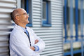 Thoughtful doctor with arms crossed smiling while leaning on wal mature hospital wall Royalty Free Stock Photo