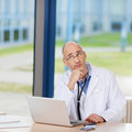 Thoughtful doctor with laptop on desk mature in clinic Stock Image