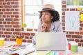 Thoughtful female interior designer at desk
