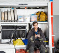 Thoughtful firewoman holding coffee mug in truck young while sitting at fire station Stock Photography