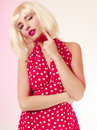 Thoughtful girl in blond wig and retro red dress winking. Pinup. Royalty Free Stock Photo