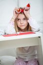 Thoughtful girl holding santa headband with pencil and cardpaper at home Royalty Free Stock Images