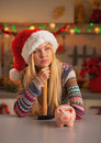 Thoughtful girl in santa hat with hammer and piggy bank portrait of teenage christmas decorated kitchen Royalty Free Stock Photo