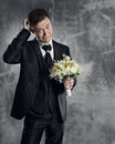 Thoughtful groom with wedding flowers bouquet gray background Stock Images