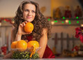 Thoughtful housewife with orange in christmas decorated kitchen young Royalty Free Stock Photo