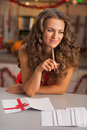Thoughtful housewife signing christmas postcards in kitchen young Royalty Free Stock Image