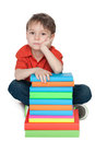 Thoughtful little boy with books a portrait of a on the floor near the pile of on the white background Royalty Free Stock Photos