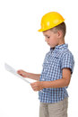 Thoughtful little builder boy in yellow hardhat and checkered shirt holding a paper plan in his hands, isolated on white Royalty Free Stock Photo
