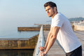 Thoughtful man athlete standing in pier in the morning Royalty Free Stock Photo