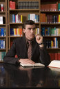 Thoughtful Man Chewing Pen At Library Desk Royalty Free Stock Photo