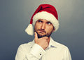 Thoughtful man in christmas hat looking up over grey background Stock Images