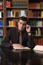 Thoughtful man at library desk young in formals with book and pen in Royalty Free Stock Photos