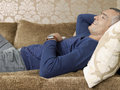 Thoughtful man with remote control while lying on sofa side view of at home Royalty Free Stock Image
