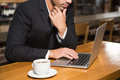 Thoughtful man using laptop and having a coffee in pub Royalty Free Stock Photo