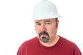 Thoughtful man wearing a hardhat staring at the camera with an uncertain analytical expression as he struggles to believe Stock Image