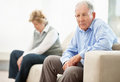 Thoughtful mature couple sitting on sofa Stock Images