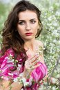 Thoughtful nice brunette portrait of posing in flowering trees Stock Images