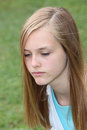 Thoughtful sad teenage girl with a serious expression and downcast eyes closeup head portrait outdoors against grass Royalty Free Stock Photography