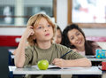 Thoughtful schoolboy scratching head his while looking away at desk in classroom Stock Images