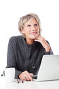 Thoughtful senior woman with a laptop sitting at desk her chin on her hand looking upwards open in front of her on white Royalty Free Stock Images