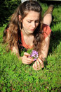 Thoughtful teen lounging a pretty tween girl with long brown hair in the grass with thoughts in her head shallow depth of field Stock Photography